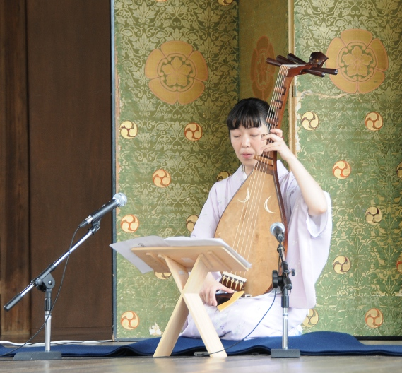 a woman playing on a biwa