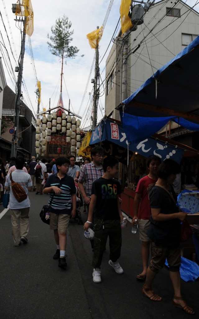 street scene with food stalls and float in the background