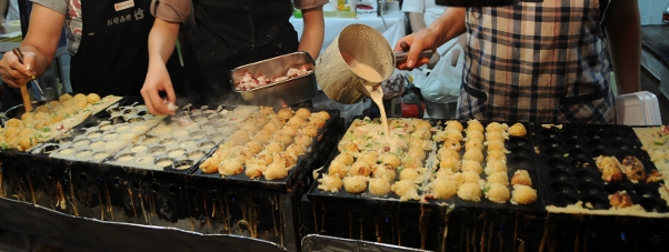 street vendors making takoyaki