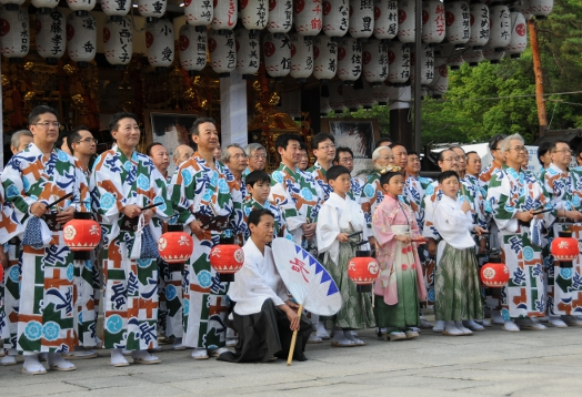 Members of the Naginata-hoko posing before the three Mikoshi