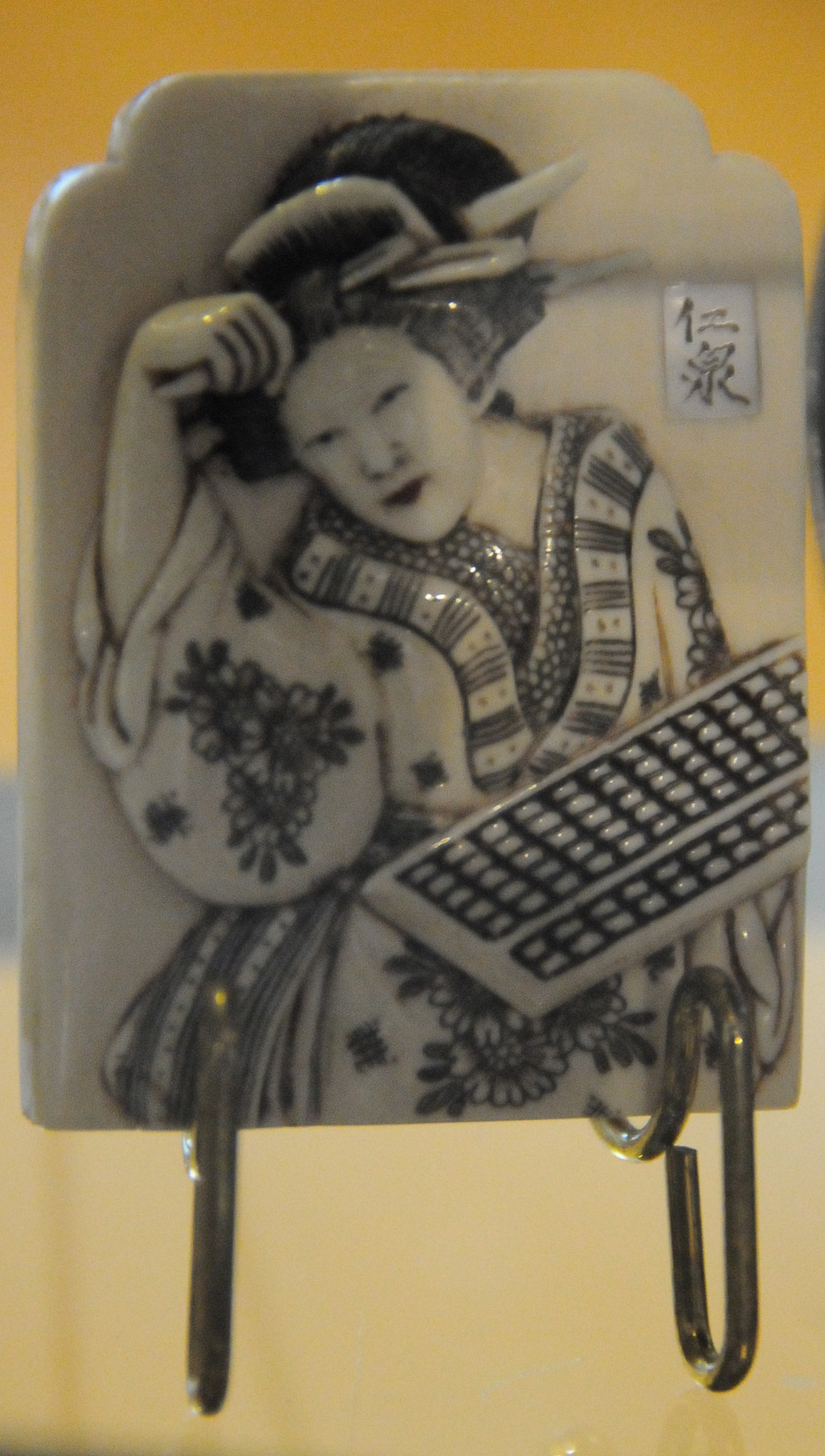 piece of ceramic jewelry depicting a woman holding a soroban